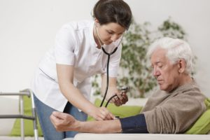 48766091 - young nurse taking old man's blood pressure